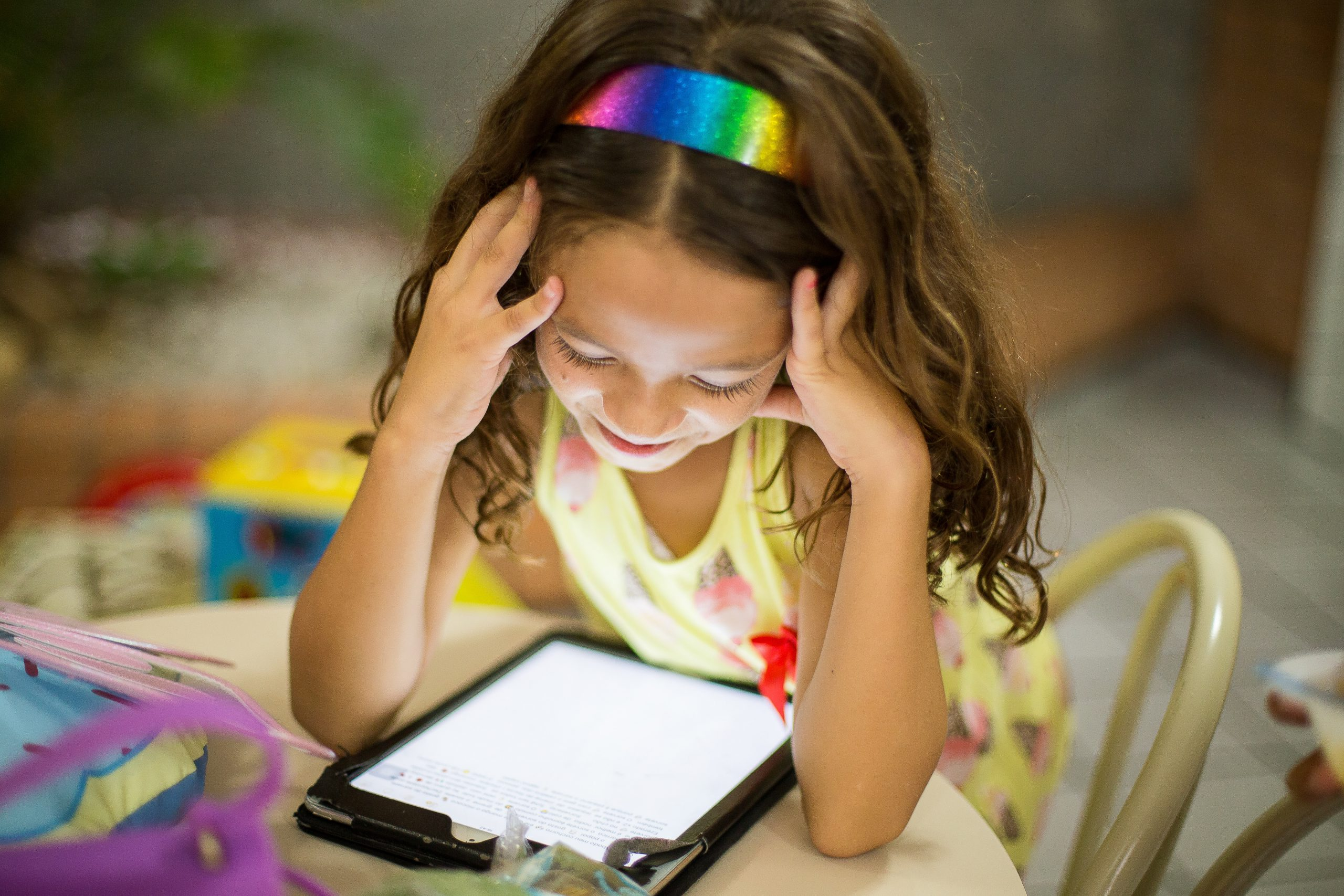 A Girl in yellow Sitting on chair and Reading the digital content from Tablet
