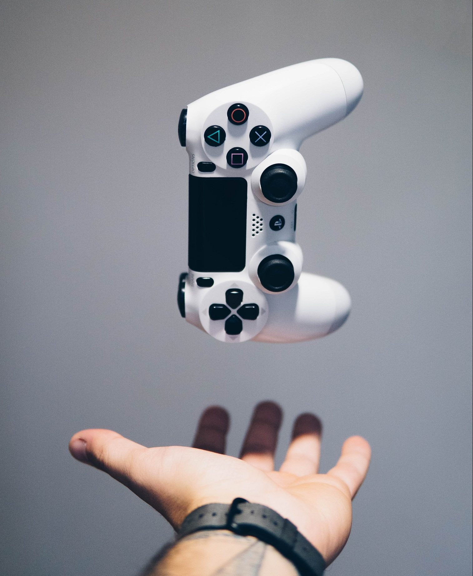 Video game controller being dropped into the palm of a hand