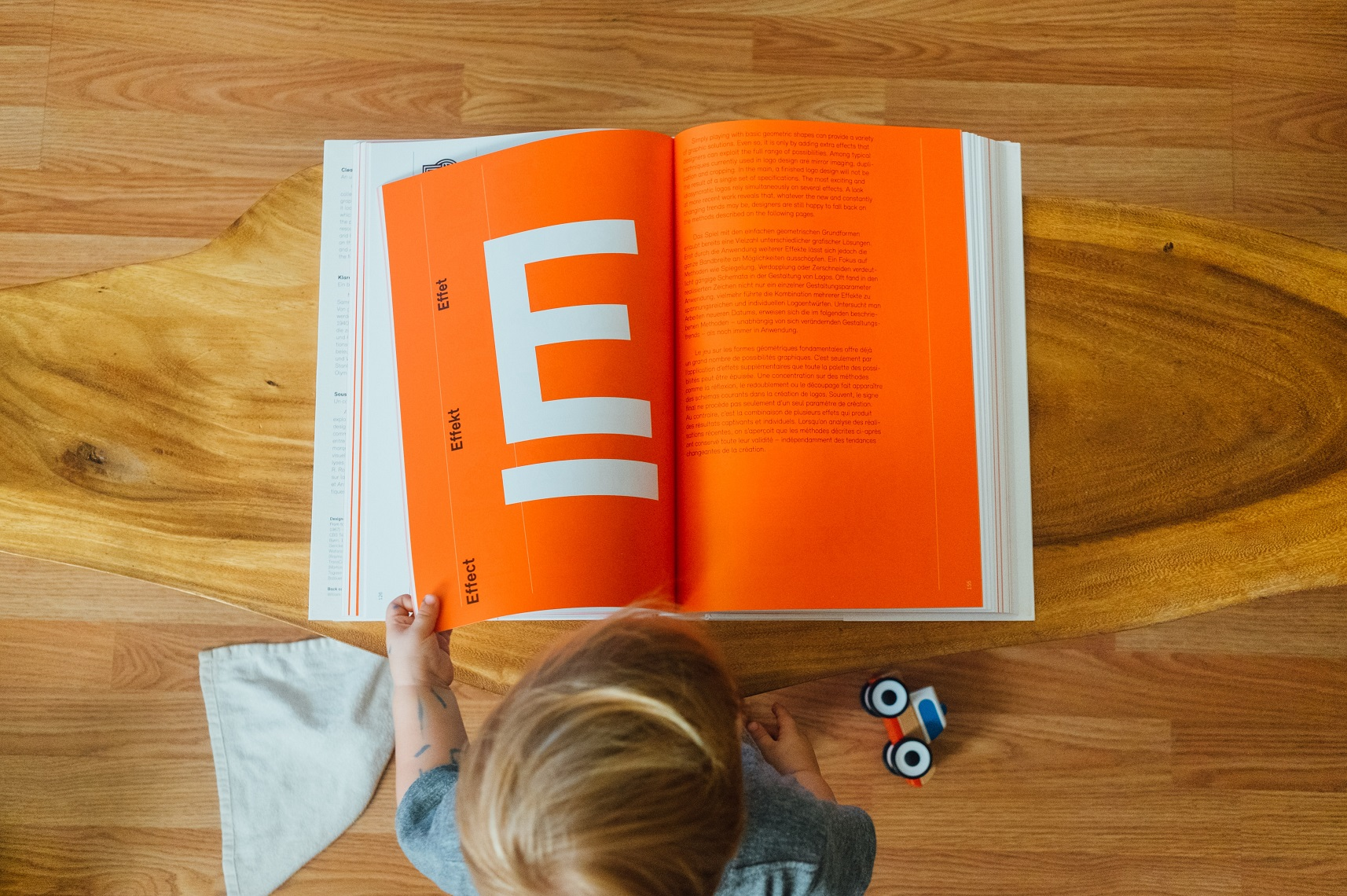 Top view of the Child holding an open book's page having a letter E on it, and a toy lying behind the book.