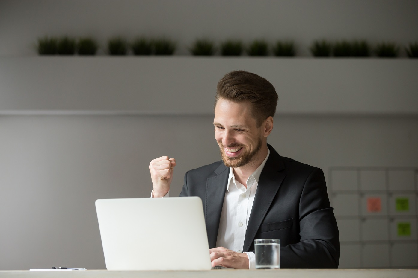 Person sitting at a laptop smiling and clenching his fist