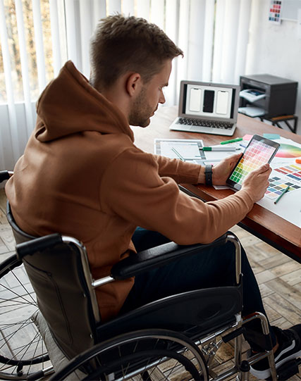 Person sitting at a desk while looking at a tablet